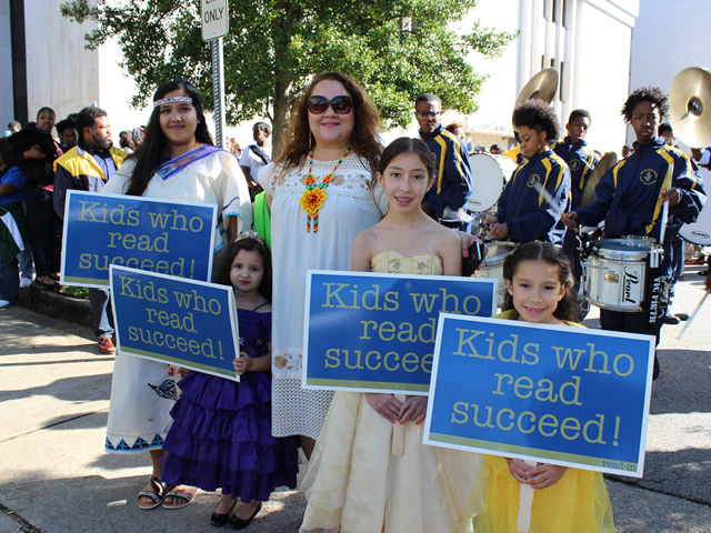 Photo of children at the Read-In in costume holding Kids Who Read Succeed signs.